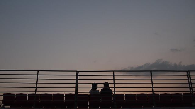 Dvaja ľudia sedia za zábradlím pri západe slnka.jpg