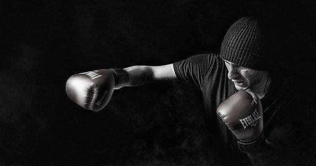 Muž s čiapkou na hlave, v boxerských rukaviciach boxuje do prázdna.jpg
