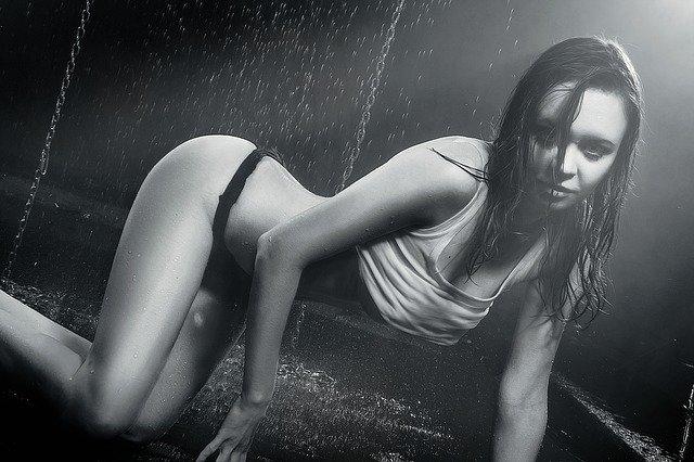 Žena v bielom tielku, čiernych nohavičkách kľačí na kolenách a tečie na ňu voda.jpg